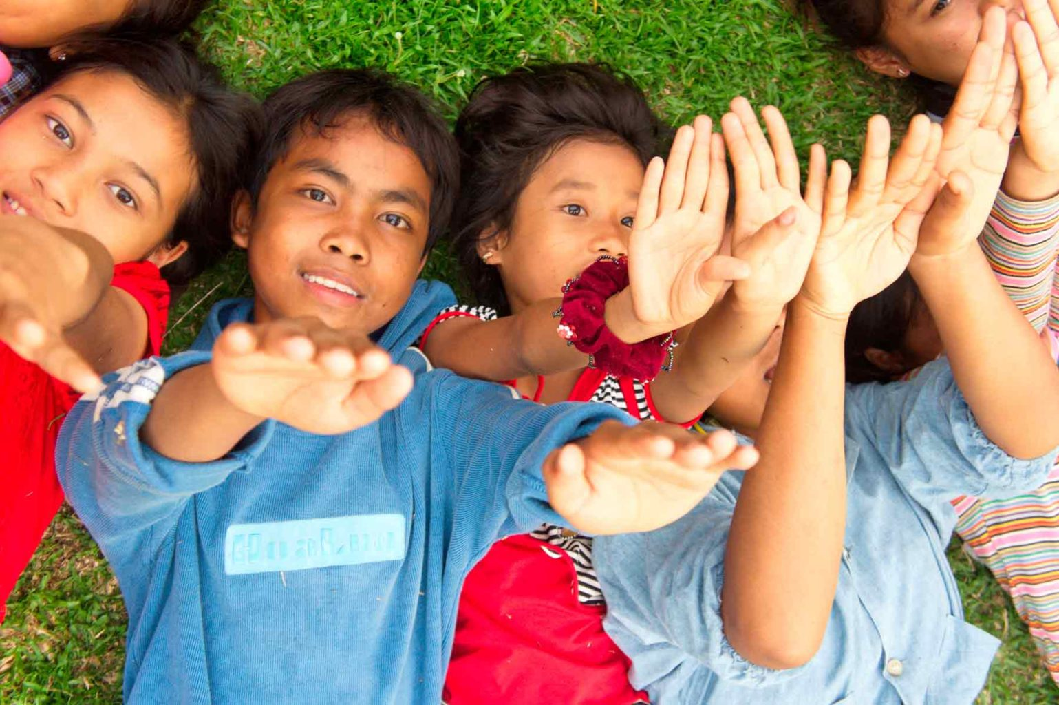 children from the shelter in Cambodia playing with their hands up