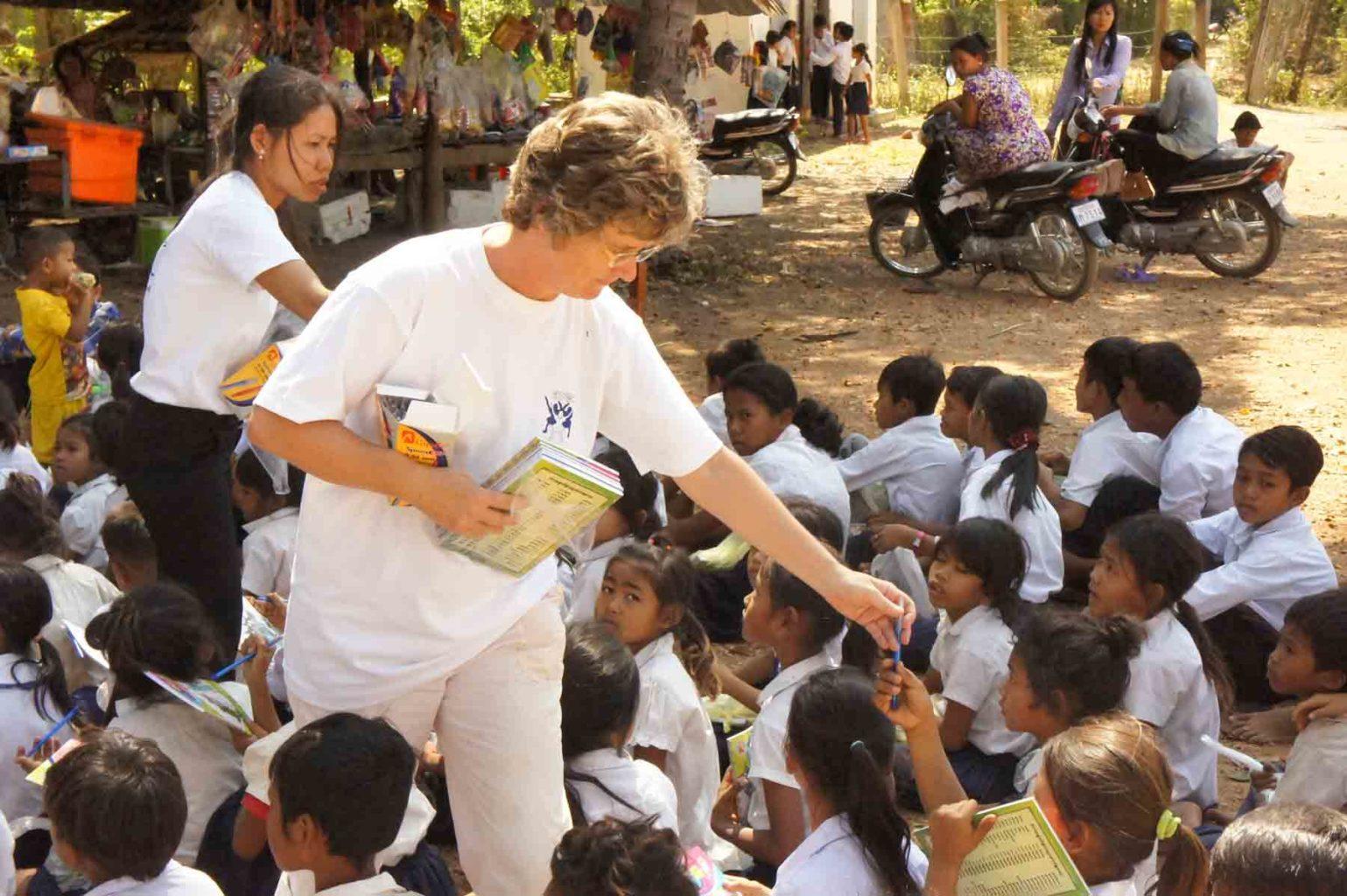 La neuchâteloise Nicole Reinhardt distribue du matériel scolaire à des enfants dans une école
